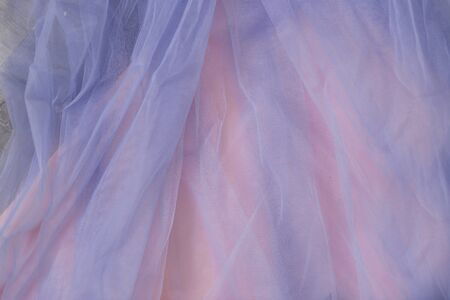 Closeup of thin blue tulle fabric on pink background. Wedding dresses, fabric texture
