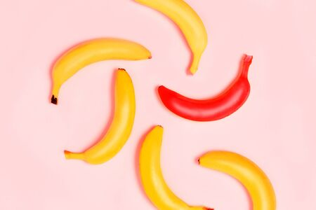 Not such as all, unique. Yellow and one red banana on blue background. From top view