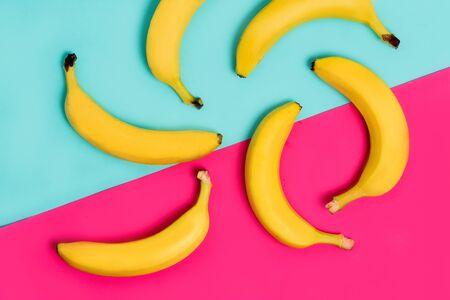 Buntes Fruchtmuster von frischen gelben Bananen auf rosa und pastellblauem Hintergrund. Von oben Standard-Bild