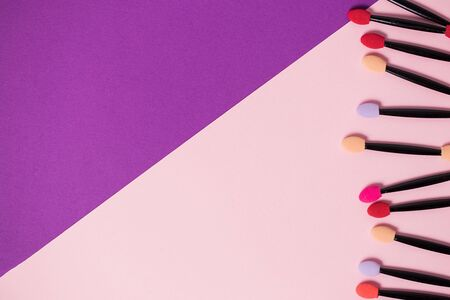 Lots of colorful eyeshadow applicators on a bright purple pink two tone background with copy space. Cosmetics, beauty, youth, care, professional makeup artist concept Stok Fotoğraf