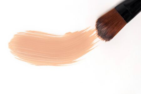 Closeup smeared beige cream with brush on white background Banco de Imagens