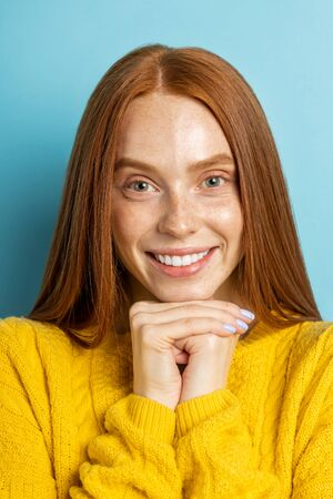 Vertical closeup portrait of cheerful ginger young woman with freckled, clean skin without makeup, touching chin with hands smiling broadly demonstrating white teeth isolated light blue background.