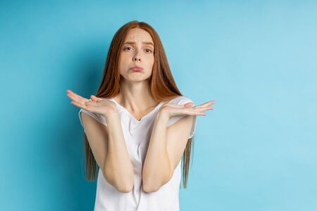 Hesitant uncertain girl with long red hair spreading palms with confused expression, wearing white tshirt, frowning face, pursing lips, cant make choice between two items isolated over blue background