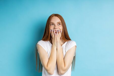 People, reaction, emotions, happiness concept. Horizontal shot of glad happy redhead young female covering mouth with both hands, smiling, having joyful dreamy expression isolated over pink background