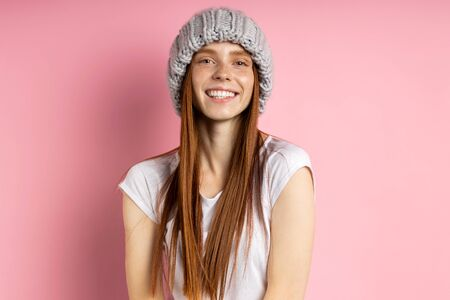 Indoor shot of good looking female model with long red hair wearing big loop knitted hat and white t shirt, smiling broadly isolated over pink background. Winter headdress, hair care concept.