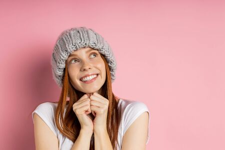 Beautiful young ginger woman with no makeup keeping hands under chin, wearing winter knitted beanie, looking aside with dreamy happy expressions isolated on pink wall. People, good emotions concept.