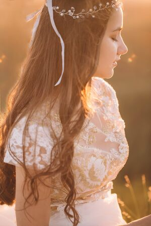 Closeup sideways portrait of a young woman in a white dress and with an ornament on her head at sunset 免版税图像