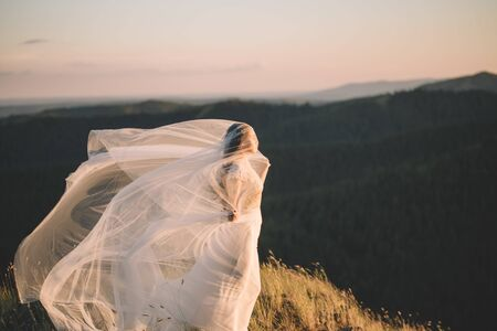 Portrait of a beautiful young brunette bride woman in a white dress and with a long veil Curling in the wind in nature, the mountains in summer. Fine art, wedding, lifestyle, love, life concept