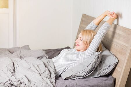 People, rest, awakening concept. Side view of caucasian sleepy woman stretching, yawning in bed, covering mouth with hand, wearing striped sleepwear, lying under gray blanket in bedroom. Фото со стока