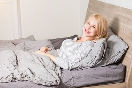 Closeup portrait of good looking young blonde woman with fresh skin waking up in good mood, posing in soft bed in bedroom, smiling joyfully looking at camera. People, rest, healthy dream concept.