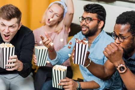 Three handsome men and cheerful blonde woman having fun, eating popcorn and enjoying together. Friends sitting on couch watching tv in modern living room at home. Leisure, home entertainment concept.