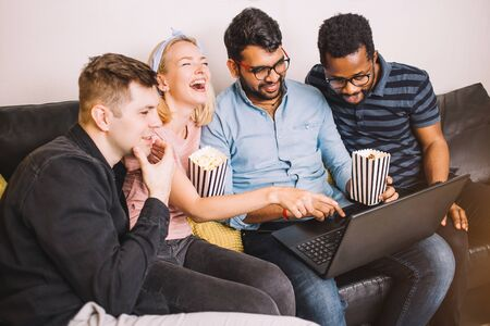 Group of young multi ethnic students preparing for exams, making presentation in apartment interior. Best friends sitting on sofa together in living room and watching movie on laptop.
