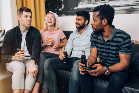 Group of diverse joyful friends having fun at home party, cheerfully laughing, enjoying drinks sitting on sofa in living room. People, leisure and friendship concept.