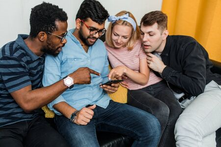 Four friends wearing casual clothes sitting on couch at home, using mobile phone together, posting on social networks and surfing the net on smartphone.