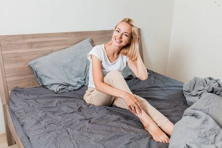 Portrait of happy laughing female awaking in good mood after healthy dream, sitting on comfortable bed in bedroom. Optimistic beautiful woman in sleepwear smiling posing in hotel room. Archivio Fotografico - 133531245