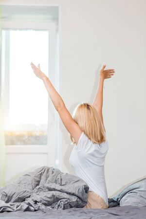 Rear shot ob blonde european woman waking up and stretching in bed with hands up, starting new day after healthy night sleep. Awakening, good morning, laziness, weekend concept. Archivio Fotografico - 133531250