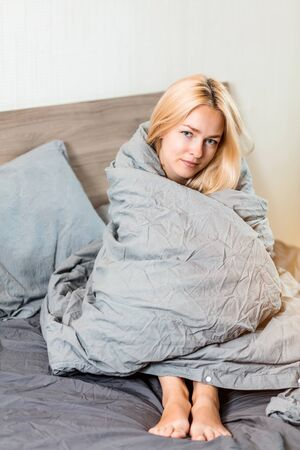 Cheerful pleased woman sitting covered with soft gray blanket looking at camera with charming smile. Portrait of blonde female lady enjoying morning in bedroom. Rest, awakening, good mood concept. Archivio Fotografico - 133531280