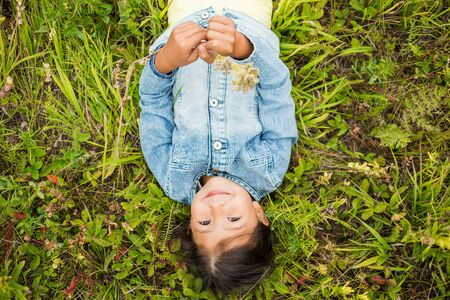 Top view portrait of a beautiful little brunette girl in blue jeans on the field, green grass in the summer nature