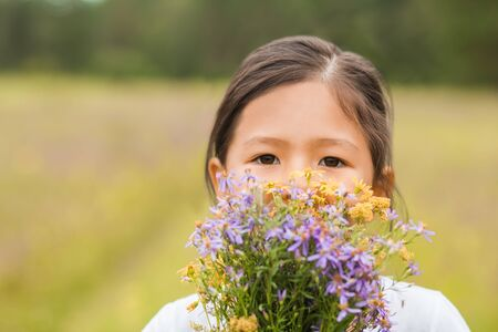 Closeup portrait of a little girl covering her face with a bouquet of wild flowers and looking at the camera in the summer in nature Imagens