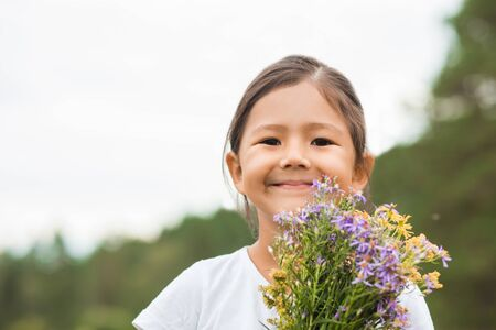 Closeup portrait of a little cute smiling girl in a white t-shirt with a bouquet on the field in summer