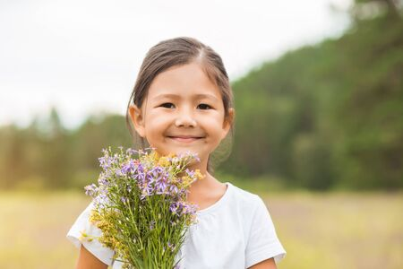 Closeup portrait of a little happy smiling girl with a bouquet on her hand on the background of the summer nature Imagens