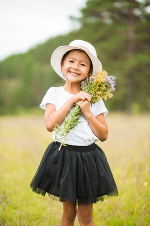 Beautiful portrait of a little cute smiling girl in a white hat and skirt with a bouquet on the field in summer Imagens