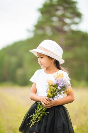 Sideways portrait of a little girl in a hat and with flowers in nature in summer