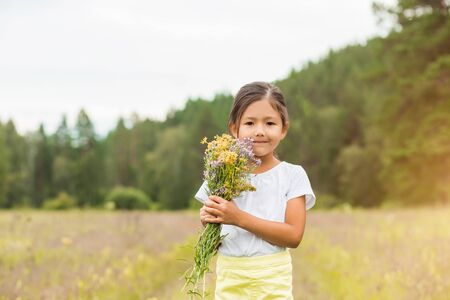Horizontal portrait of a cute little girl in a white hat, t-shirt and flowers in nature in summer Imagens