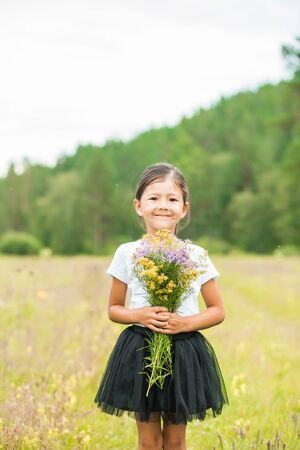 A beautiful little girl in a white t-shirt and black skirt stands in the summer in nature, smiling and holding wild flowers on her hand