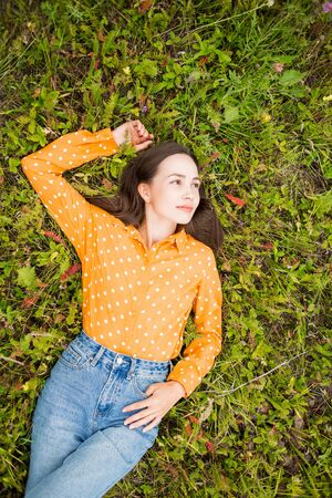 Beautiful fashionable portrait of young sexy smiling brunette woman lying on green grass, top view. Lifestyle, summer, rest, mood, happiness concepts. Copy space