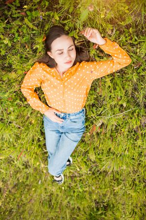 Creative portrait of beautiful woman with closed eyes on green grass background, top view. Lifestyle, summer, rest, mood, happiness concepts.