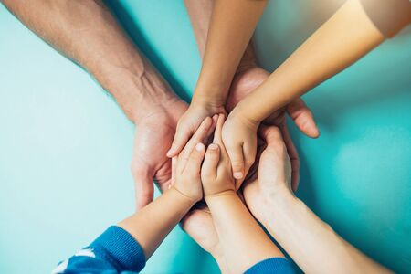 Closeup of the United hands of one family on a blue background. Dad, mom, kids holding hands. Large male hands hold the hands of his family