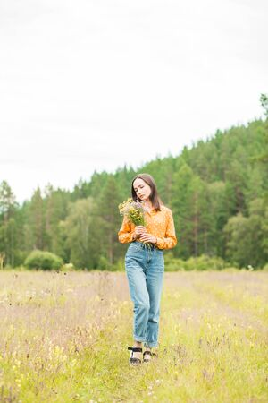 Portrait of young beautiful woman with bouquet on the hands on green background summer nature.