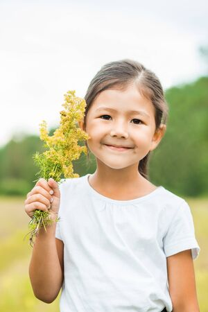 Closeup portrait of a beautiful little brunette girl with yellow flowers on her hand in nature in summer