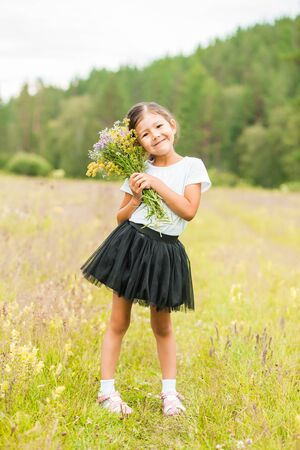 Portrait of a little brunette girl on the field with flowers on her hand