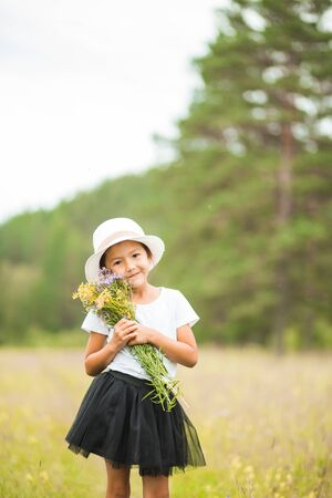Portrait of a cute little girl with flowers on her hand in nature