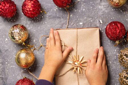 Closeup of cute little baby hands holding gift box on grey background with red and gold balls, top view. Kids, new year, Christmas, holiday concept