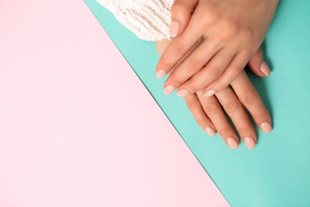 Top view beautiful hands with manicured nails on top of each other on a two tone pastel blue and pink background, closeup, copy space. Care, beauty, Spa, salon concept 写真素材