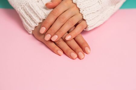 Closeup of beautiful hands, nails, delicate manicure on pink background. Care, beauty, Spa, salon concept 写真素材