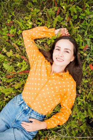 Closeup portrait of smiling beautiful sexy brunette woman on grass lying, top view. Orange blouse and blue jeans on girl. Lifestyle, summer, rest, mood, happiness concepts 写真素材
