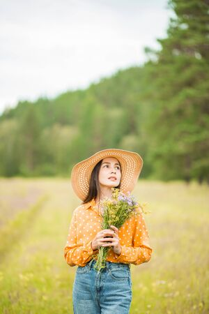 Beautiful young brunette woman in hat, orange blouse, blue jeans, with flowers on hands on the background of green nature looks up, away. Lifestyle, summer, rest, mood, happiness concepts, copy space