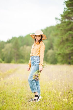 Portrait of a charming smiling and looking down brunette woman in a hat and with a bouquet of flowers on the background of summer nature. 写真素材