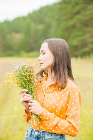 Sideways closeup portrait of a beautiful cute brunette woman sniffing wild flowers in nature in summer 写真素材