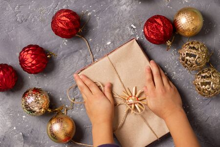 Kids, new year, Christmas, holiday concept. Little girl or boy holding gift box on grey background