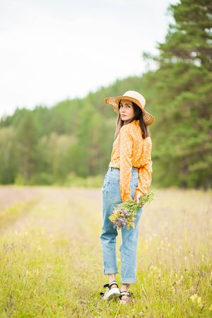 Portrait of a beautiful sexy brunette woman in a wide hat, orange blouse and jeans with flowers on her hands in nature
