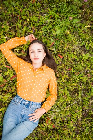 Fashion portrait of beautiful young sexy brunette woman on green grass in summer, top view. Girl lying on the ground in Orange blouse and blue jeans. Copy space