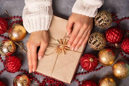 Womens hands in a warm sweater holding a gift box on a gray Christmas background with balls 写真素材