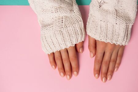 Beautiful womans hands on pink background