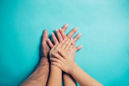 Four hands on blue background. Dad, mom, daughter and little son put their hands on each other. Family, friendship, love, heritage concept