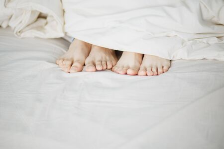 the legs of two lovers men and women protrude protrude under the white soft fluffy clean blanket on the bed